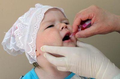 девочке капают в рот вакцину