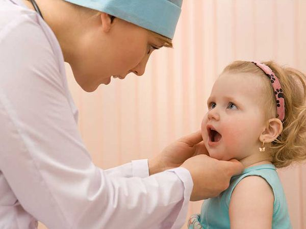 врач осматривает полость рта девочки